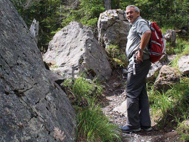 Wanderweg durch den Wald, im Vordergrund ein grosser Felsblock.