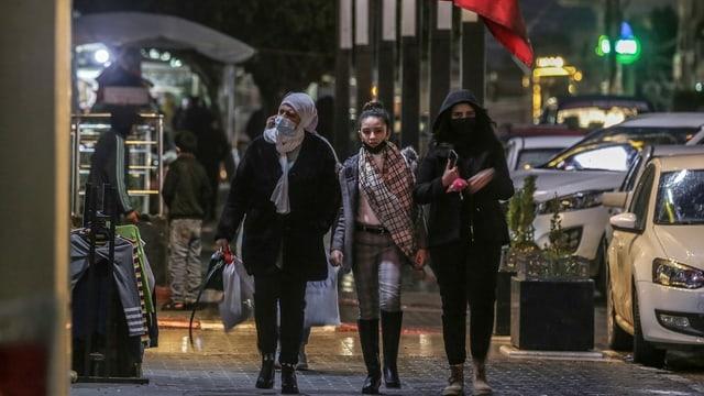 Drei junge Frauen spazieren auf einer Strasse.