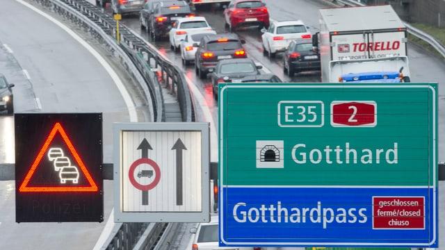 Autokolonne von oben aufgenommen, im Vordergrund Anzeigetafel mit Hinweis auf den Gotthardtunnel und Gotthardpasss sowie Stauwarnung