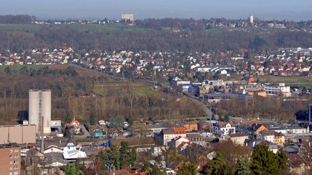 Die Gemeinde Münchenstein von oben gesehen, links hohe Kamine, im Hintergrund Häuser