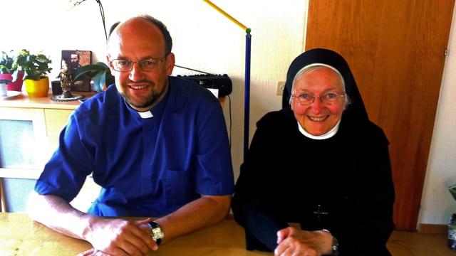 Dorfpfarrer Edi Arnold und Schwester Pirmine sitzen nebeneinander an einem Tisch.