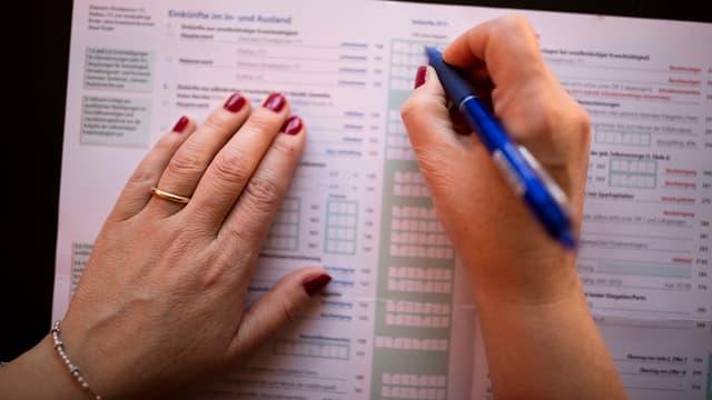Frauenhände, welche eine Steuererklärung ausfüllen.