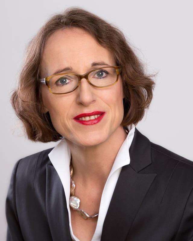 Jutta von Falkenhausen mit Brille lächelt in die Kamera.