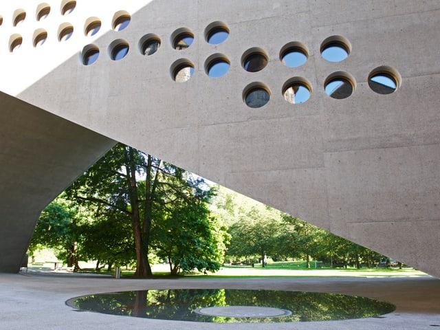 Im Vordergrund eine runde Wasserfläche, darüber spannt sich der Verbindungsbau, unter dem hindurch die Bäume des Parkes sichtbar sind.