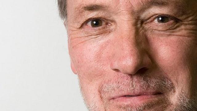 Nahaufnahme der Schweizer Schriftstellers Urs Faes, eines Mannes mit Dreitage-Bart und braunen Augen.