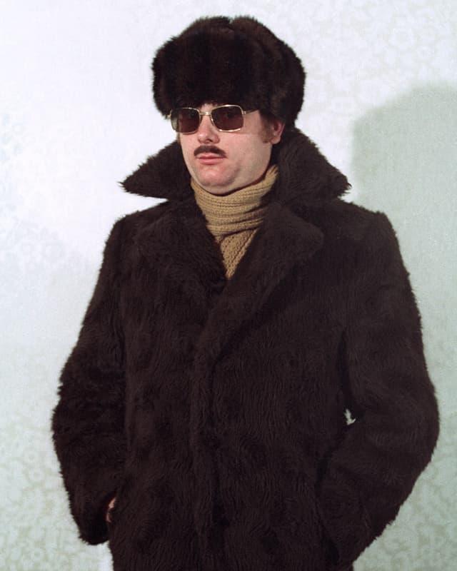Ein Mann mit Perlzmantel und -Mütze und mit Sonnenbrille