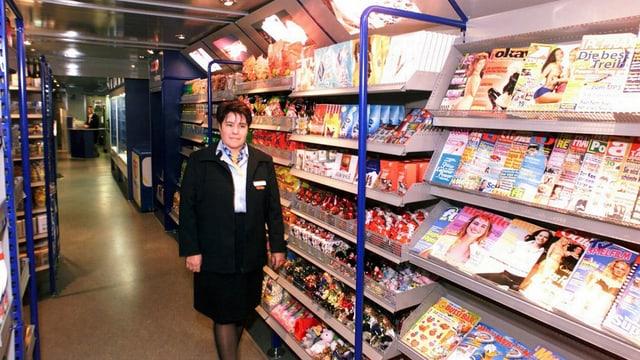 Eine Frau in Uniform steht in einem Zugwagen, der mit gefüllten Regalen ausgestattet ist.