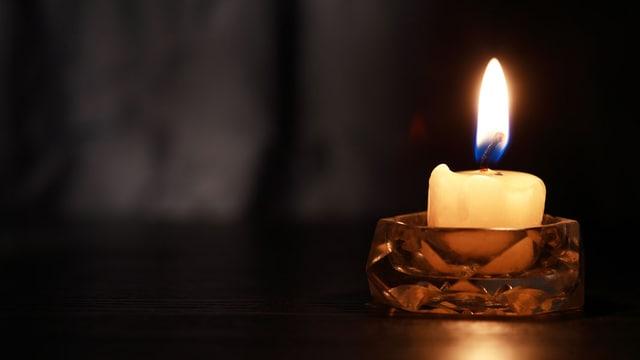 Brennende Kerze im Dunkeln.