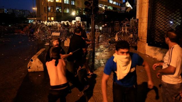 Einige Demonstraten, ein junger Mann mit einem weissen Tuch um Nase und Mund, hinten eine Polizeikolonne mit Schutzschildern.
