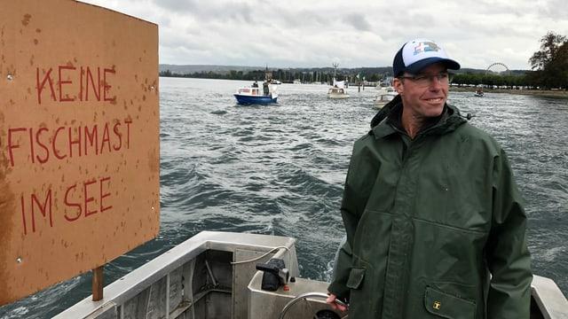 Person auf einem Schiff mit Plakat.