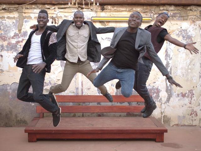 Vier junge Männer springen in die Luft.