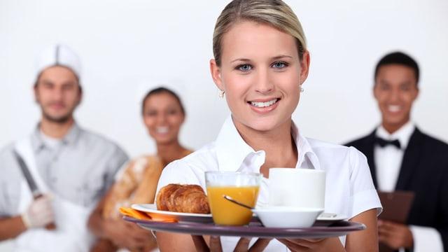 Restaurantpersonal, im Vordergrund eine Kellnerin.