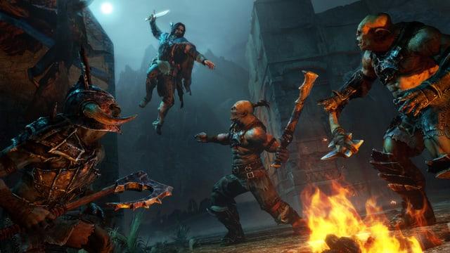 Talion springt Dolch voraus auf eine Gruppe Orks am Lagerfeuer.