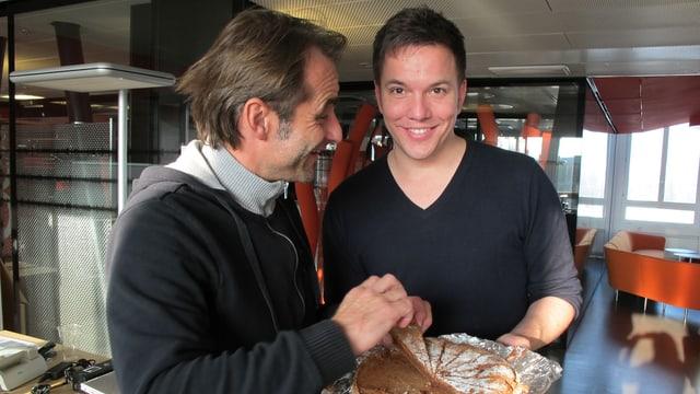 Sven offeriert seinem Kollegen Thomy Scherrer ein Stück Schoggikuchen.