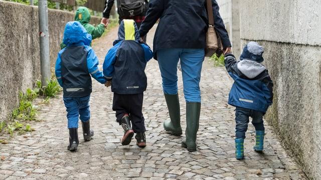 Frau mit Kindern an der Hand, von hinten fotografiert.