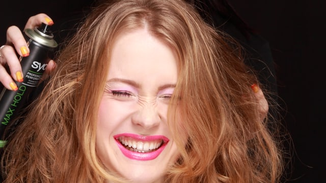 Frau kriegt Haarspray auf die Haare