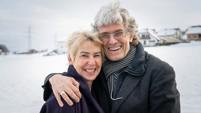 ein Mann lacht und umarmt seine Frau, die neben ihm steht