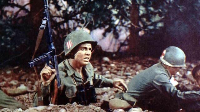 Zwei Soldaten in Uniform und mit Helm im Schützengraben, der eine kehrt der Kamera den Rücken zu, der andere hält sein Gewehr in die Höhe