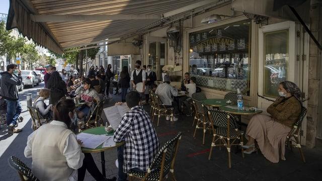 Menschen sitzen an Restaurant-Tischen.