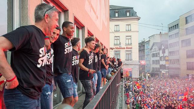 Männer stehen auf Balkon, zahlreiche Menschen feiern auf dem darunterliegenden Platz
