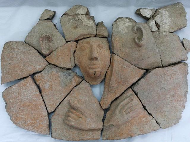 Einzelne Tonscherben, im Zentrum das Relief eines Menschen.