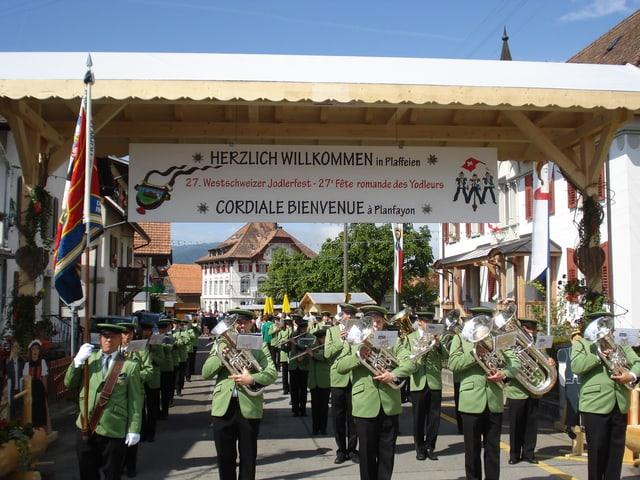Grün uniformierte Blasmusikanten marschieren musizierend durchs Dorf.