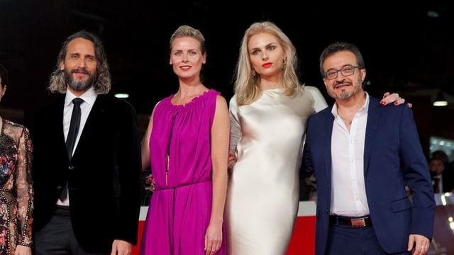 Szene vom roten Teppich: Zwei Männer und zwei Frauen posieren miteinander. Die zweite Frau von rechts hat lange blonde Haare und trägt ein hautenges Kleid. Sie hat einen Arm um den Mann links von ihr gelegt.