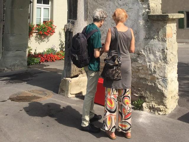 Ein Mann und eine Frau betrachten einen rot eingefärbten Koffer, der am Boden steht.