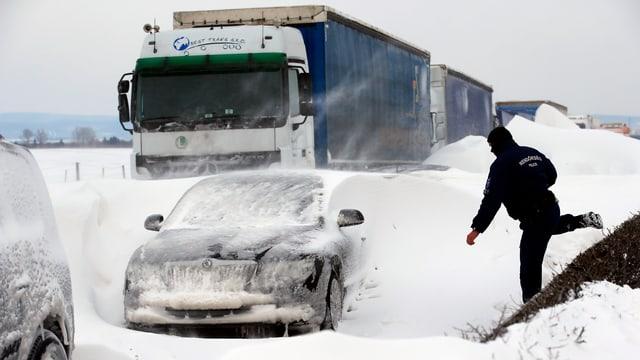 Ein Polizist steigt über Schneemassen zu den eingeschneiten Autos.