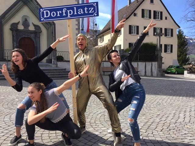Vier junge Menschen mit einem Schild, auf dem «Dorfplatz» steht.