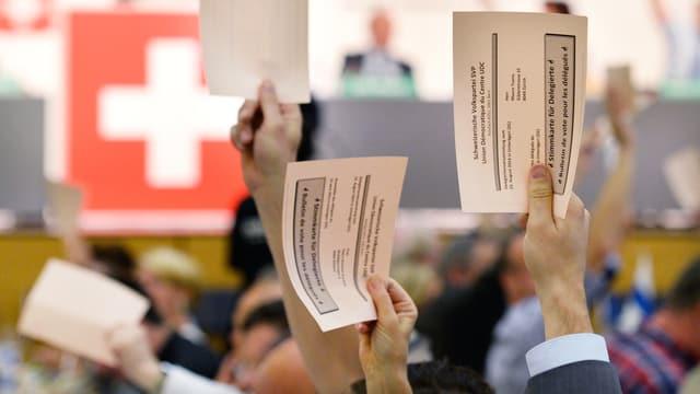 Mehrere Männer halten an der Versammlung der SVP weisse Wahlkarten in die Höhe, im Hintergrund eine Schweizer Flagge.