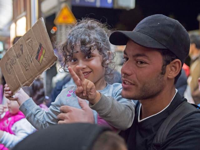 """Ein Mädchen hält ein """"Germany Love""""-Schild hoch und macht das Peace-Zeichen."""