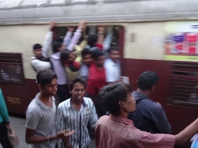 Männer halten sich an der Türe des Zuges fest und lehnen nach draussen, damit sie noch mitfahren können.