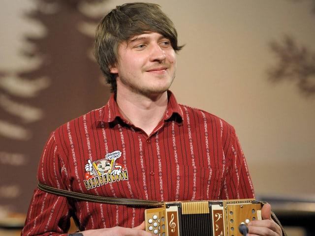 Der Musiker im roten Hemd mit feinen weissen Streifen und dem Aufdruck «Schabernack» beim Schwyzerörgeli-Spiel.