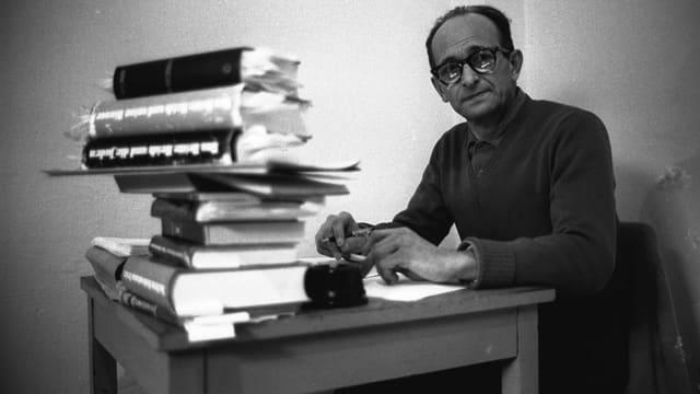 Adolf Eichmann hinter einem Stapel Bücher.
