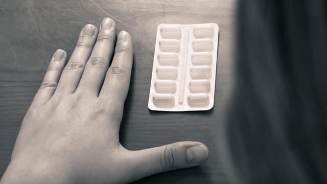 Eine Hand neben einer Packung Tabletten.