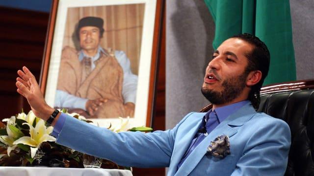 Saadi sitzend in blauem Anzug referiert gestikulierten mit dem rechten Arm, hinter ihm ein Foto seines Vaters Muammar..