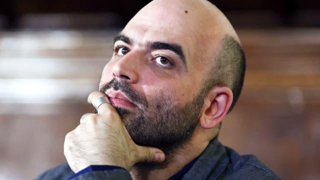 Autor Roberto Saviano stützt sein Kinn in die Hand und hat einen nachdenkliche Blick.