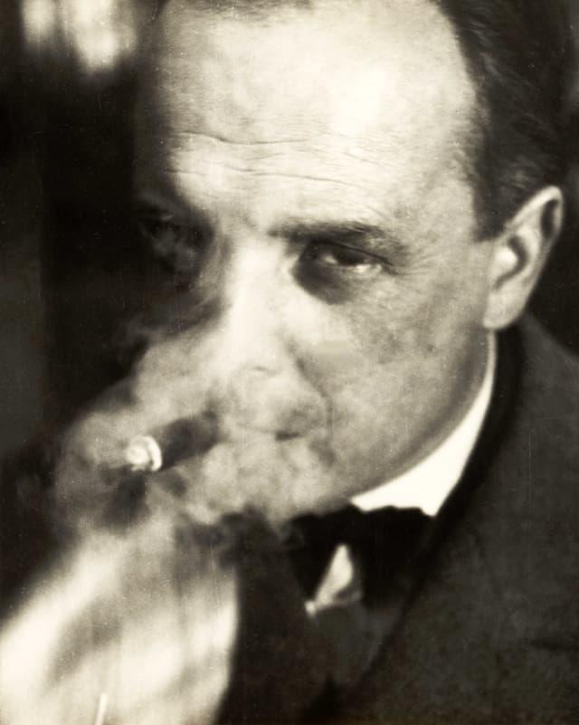 Paul Klee, der durch den Rauch seiner Zigarette blickt.