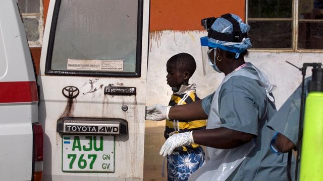 Ein Helfer eskortiert einen Buben mit Verdacht auf Ebola zu einer Ambulanz.