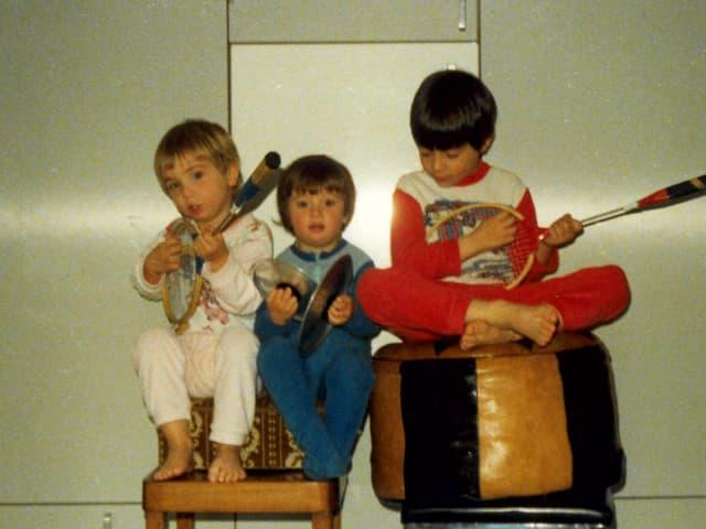 Drei Kinder im Pajama mit Tennisschlägern als Ersatzinstrumente.