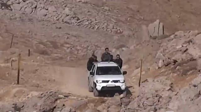 Pick-up-Fahrzeug mit Männern auf einer staubigen Bergstrasse.