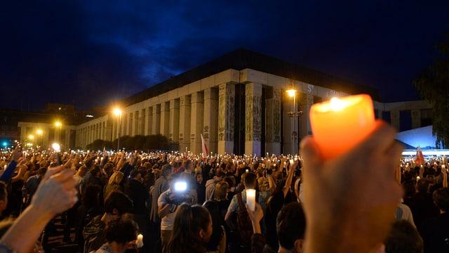 Menschenmenge vor einem grossen Gebäude stehend und Kerzen in die Luft haltend