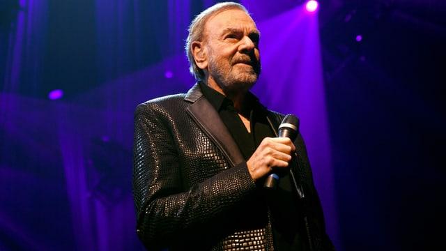 Neil Diamond mit Mikrophon in der Hand im Scheinwerferlicht einer Bühne.