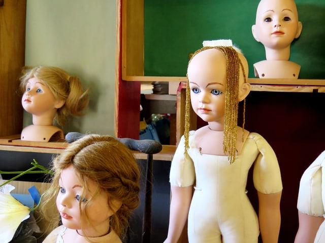 Puppen mit Goldketten auf dem Kopf im Materialmarkt Offcut.