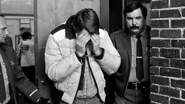 Ein Mann in Handschellen verdeckt mit beiden Händen sein Gesicht, während er von einem Polizisten durch eine Tür geführt wird.
