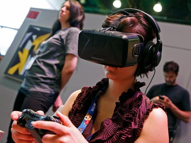 Eine Frau trägt beim Gamen eine Entwickler-Version der Oculus Rift Virtual-Reality-Brille.
