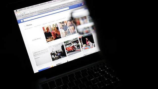 Jemand mit Brille sitzt vor einem Computerbildschirm, auf dem eine Facebookseite zu erkennen ist.