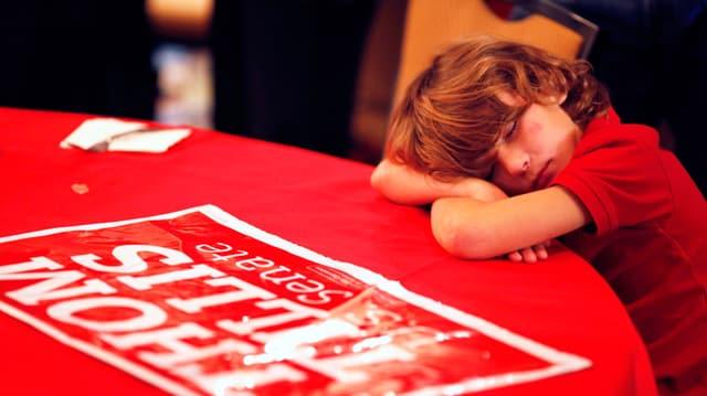 Ein schlafender Junge am Tisch