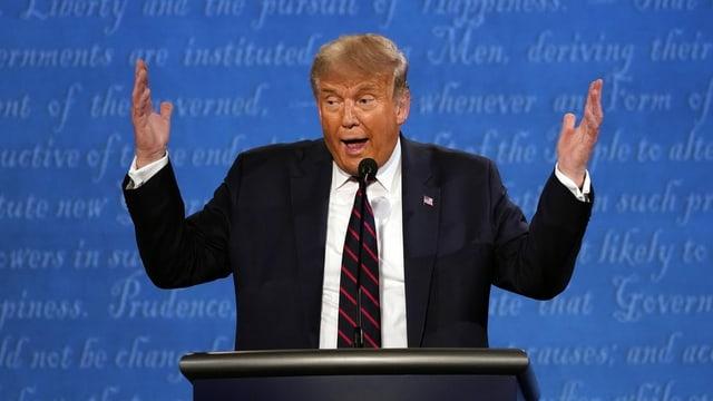 Ein Mann steht im Anzug vor einem Sprecherpult und wirft die Hände in die Luft.